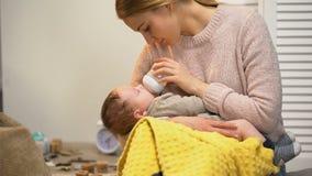 Молодая дама кладя ребенка для того чтобы спать, накормленныйся от бутылки с младенческой формулой акции видеоматериалы