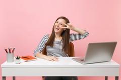 Молодая смеясь женщина в случайных одеждах показывая знак победы сидит и работает на белом столе с современным ноутбуком ПК стоковые изображения