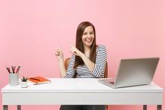 Молодая смеясь женщина в случайных одеждах указывает указательный палец в сторону сидит, работа на белом столе с современным ноут стоковая фотография