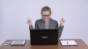 Молодая счастливая белокурая коммерсантка используя ноутбук и получающ хорошие новости на работе акции видеоматериалы