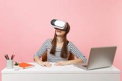 Молодая усмехаясь женщина в случайных одеждах, шлемофон виртуальной реальности на голове сидеть и работать на белом столе с ноутб стоковое изображение