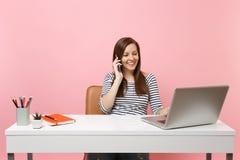 Молодая усмехаясь женщина говоря на мобильном телефоне, проводя приятный разговор сидит, работающ на офисе с ноутбуком ПК стоковое фото rf