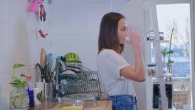 Молодая sporty женщина выпивает ясную свежую воду в кухне стоковые изображения rf