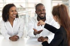 Молодые африканские пары начиная семейная жизнь получая ключи от риэлтора стоковые изображения rf