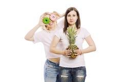 Молодые женщины с ананасом и тортами в их руках, трудном выборе белизна изолированная предпосылкой стоковые изображения