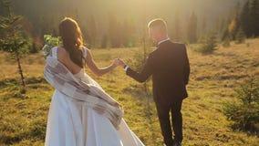Молодые и красивые пары свадьбы совместно на наклоне mountainat на заходе солнца Прекрасный выхольте и невеста ветрено сток-видео