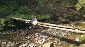 Молодые и красивые пары совместно сидят на мосте над небольшим рекой в парке Погода лета Стрельба от воздуха видеоматериал