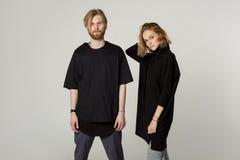 Молодые красивые пары в черных футболках представляя в студии стоковые изображения