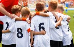 Молодые мальчики в футбольной команде Группа в составе дети в футбольной команде Речь Coach's футбола школы Pregame стоковые изображения rf