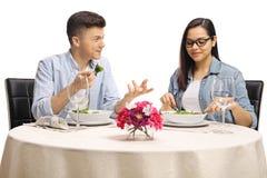 Молодые мужчина и женский ел салат на таблице и говорить ресторана стоковая фотография