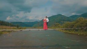 Молодые пары совместно на мосте над рекой Погода лета пасмурная Стрельба от воздуха акции видеоматериалы