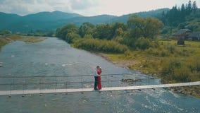 Молодые пары совместно на мосте над рекой Погода лета пасмурная Стрельба от воздуха видеоматериал