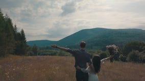 Молодые пары совместно на поле с цветками Погода лета Стрельба от воздуха Воздушная съемка акции видеоматериалы