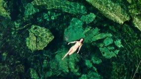 Молодые поплавки и игры женщины брюнета в естественном бассейне cenote в Мексике сток-видео