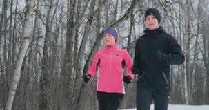 Молодые человек и женщина пар семьи на jog утра в женщине леса a зимы в свободной куртке человек в черноте видеоматериал