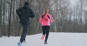 Молодые человек и женщина пар семьи на jog утра в женщине леса a зимы в свободной куртке человек в черноте сток-видео