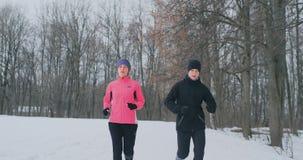 Молодые человек и женщина пар семьи на jog утра в женщине леса a зимы в свободной куртке человек в черноте акции видеоматериалы