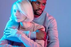 Молодые multiracial пары обнимая над голубой предпосылкой стоковое изображение