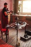 Молодое положение сапожника около стола с полезными инструментами в мастерской стоковое изображение