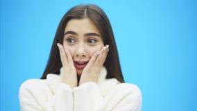 Молодое хорошее положение девушки дела на голубой предпосылке Во время ее сюрприза, она кладет ее руки на ее щеки акции видеоматериалы