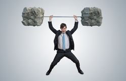 Молодой бизнесмен в костюме поднимает тяжелые весы стоковое фото rf