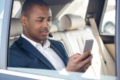 Молодой бизнесмен сидя в окне автомобиля раскрыл проверку социальных средств массовой информации на усмехаться смартфона радостны стоковая фотография