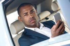Молодой бизнесмен сидя в окне автомобиля раскрыл смартфон просматривать смотря конец-вверх камеры внимательный стоковая фотография rf