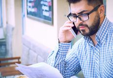 Молодой бородатый бизнесмен в случайных одеждах и eyeglasses изучает документ пока говорящ на сидеть смартфона стоковые фотографии rf