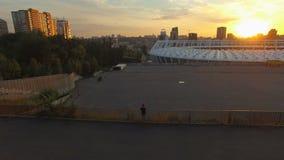 Молодой вентилятор смотрит на Olympic Stadium Арена и городской пейзаж футбола на антенне захода солнца сток-видео