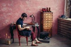 Молодой внушительный человек позаботится о ботинки стоковое изображение rf