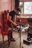 Молодой внушительный человек очищая ботинки стоковое фото