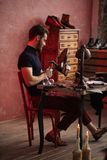 Молодой жизнерадостный человек ремонтируя пятку ботинка стоковые изображения