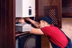 Молодой квалифицированный рабочий регулирует боилер газа перед использованием стоковые фото