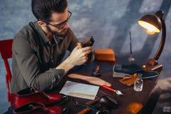 Молодой красивый человек общаясь с инструментом сапожника, закрывает вверх по изображению стоковая фотография