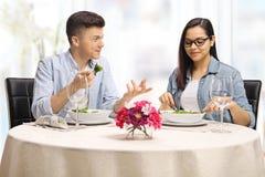 Молодой мужчина и женщина есть на ресторане и говорить стоковые фотографии rf