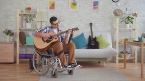 Молодой неработающий человек в музыканте кресло-коляскы играет гитару акции видеоматериалы