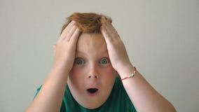 Молодой парень схватывает его голову показывая утеху и наслаждение на стороне Прелестный мальчик смотрит в камеру с эмоциями и чу акции видеоматериалы