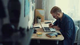 Молодой привлекательный человек со стеклами и желтыми волосами используя ноутбук в домашнем офисе и делает примечания на стикере  сток-видео