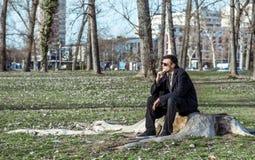 Молодой сиротливый подавленный и встревоженный человек сидя самостоятельно в парке на деревянном пне разочарованном в его жизни п стоковая фотография