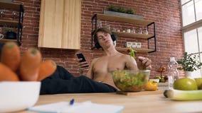 Молодой спортсмен с нагим торсом сидя за кухонным столом есть салат vegan пока слушая музыка в наушниках и сток-видео