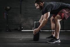 Молодой спортсмен crossfit подготавливая вес штанги поднимаясь на спортзале Облако пыли предохранения от магнезии Красивый челове стоковая фотография rf
