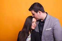 Молодой супруг показывая его привязанность к ее жене над желтой предпосылкой стоковая фотография