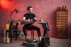 Молодой творческий сапожник изобретая стильные ботинки стоковая фотография