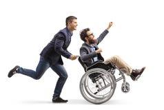 Молодой человек бежать и нажимая возбужденного человека в кресло-коляске показывая жестами с рукой стоковые изображения rf