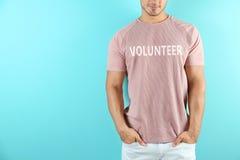 Молодой человек в футболке на предпосылке цвета стоковое фото