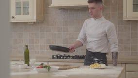 Молодой человек в форме шеф-повара кладет соль в лоток fryng и бросает вверх мясо в skillet Профессиональный повар варя еду на акции видеоматериалы