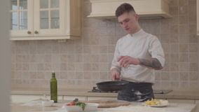 Молодой человек в форме шеф-повара кладет соль в лоток fryng и бросает вверх мясо в skillet Профессиональный повар льет молоко видеоматериал