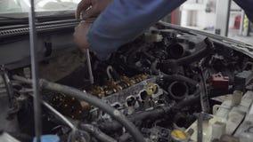 Молодой человек закручивает с помощью инструменту двигатель от автоматического механика ремонтирует автомобиль для того он к акции видеоматериалы