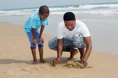 Молодой человек и его сын на пляже стоковая фотография
