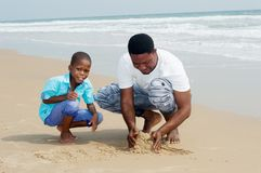 Молодой человек и его сын на пляже стоковая фотография rf